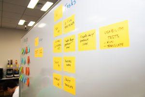 WordCamp Tokyo 2018 Contributor Day のデザインチームで活用されていたホワイトボードに人やタスクの書かれたポストイットが貼ってある。