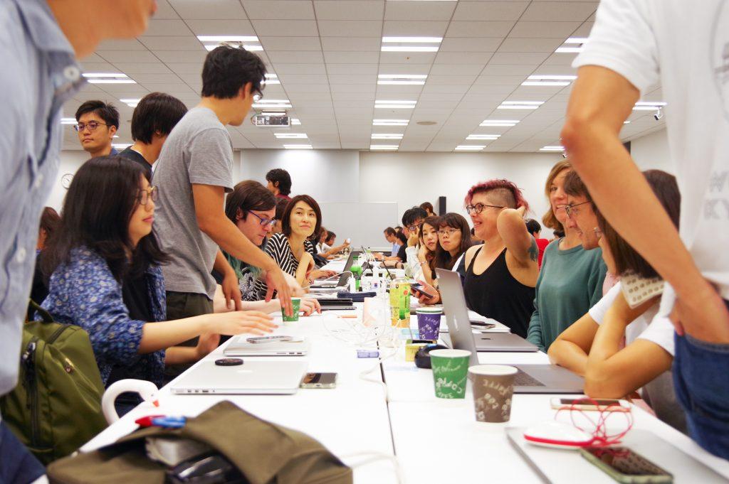 写真: 長テーブルを囲む人々。